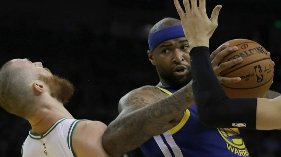 The Golden State Warriors' DeMarcus Cousins, center, fouls Boston Celtics' Aron Baynes, left, during the first half March 5, 2019, at Oracle Arena in Oakland, California.