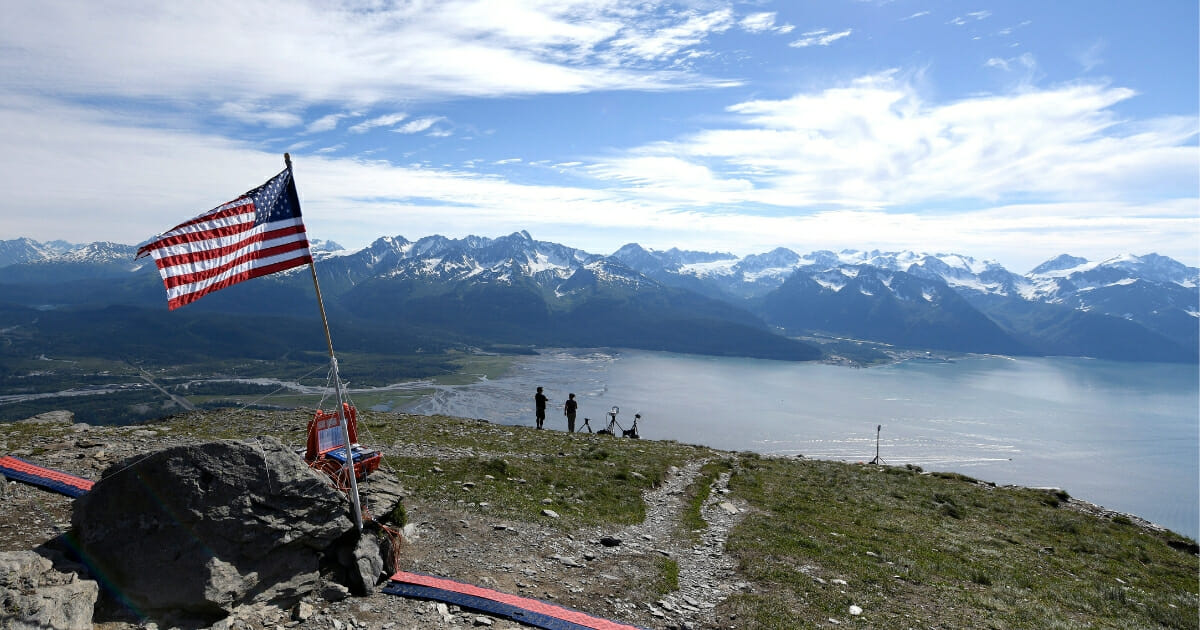 American flag on mountain top.