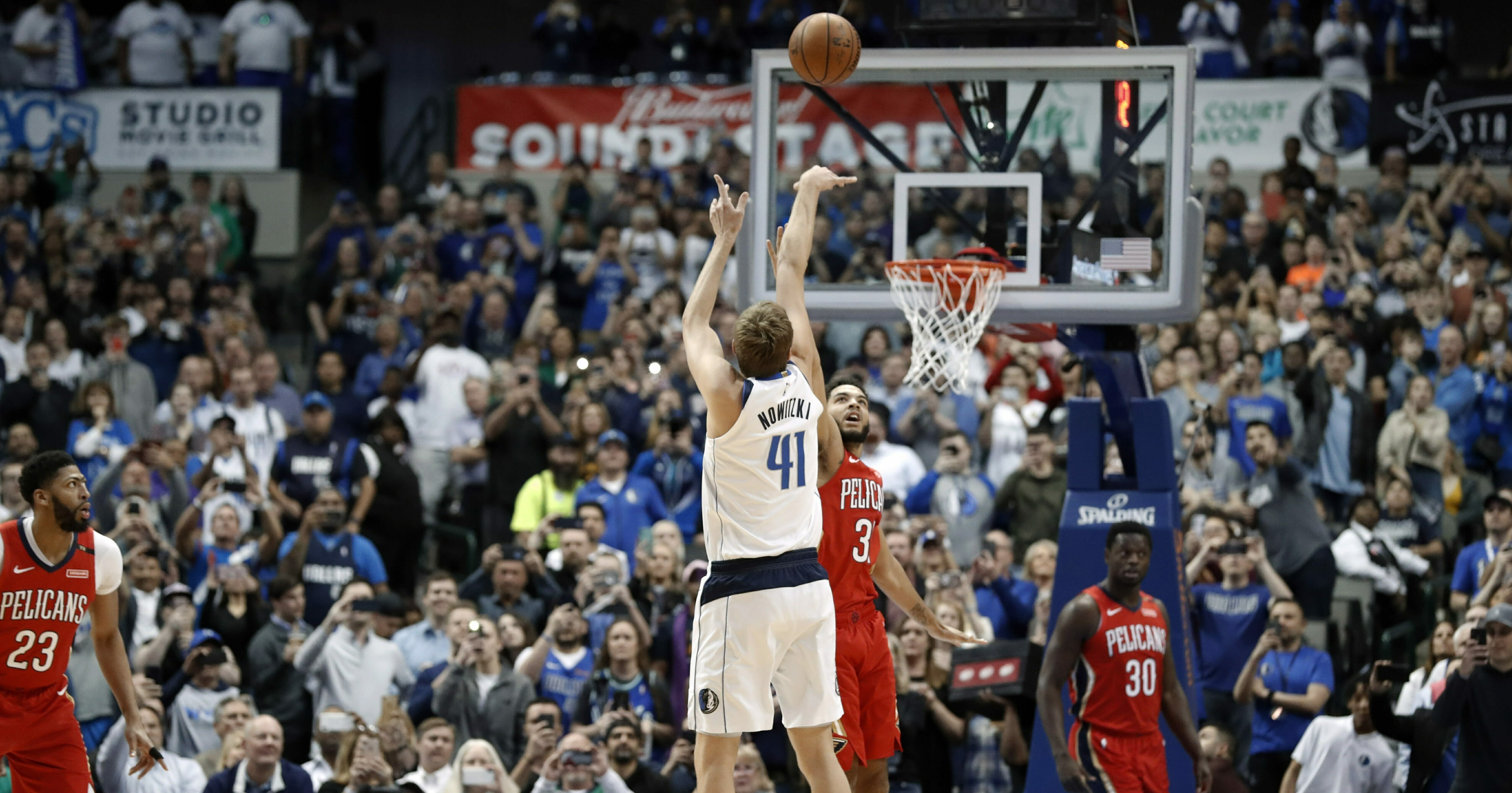 Dallas Mavericks forward Dirk Nowitzki shoots as New Orleans Pelicans' Kenrich Williams defends in the first half of an NBA basketball game in Dallas, Monday, March 18, 2019.