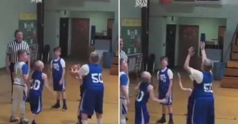 Teammate helps boy with cerebral palsy shoot a basket.