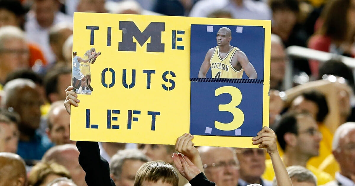 A fan holds up a sign which reads as a TImeout counter in reference to former Michigan Wolverines player Chris Webber as Michigan plays against the Syracuse Orange at the Georgia Dome on April 6, 2013 in Atlanta