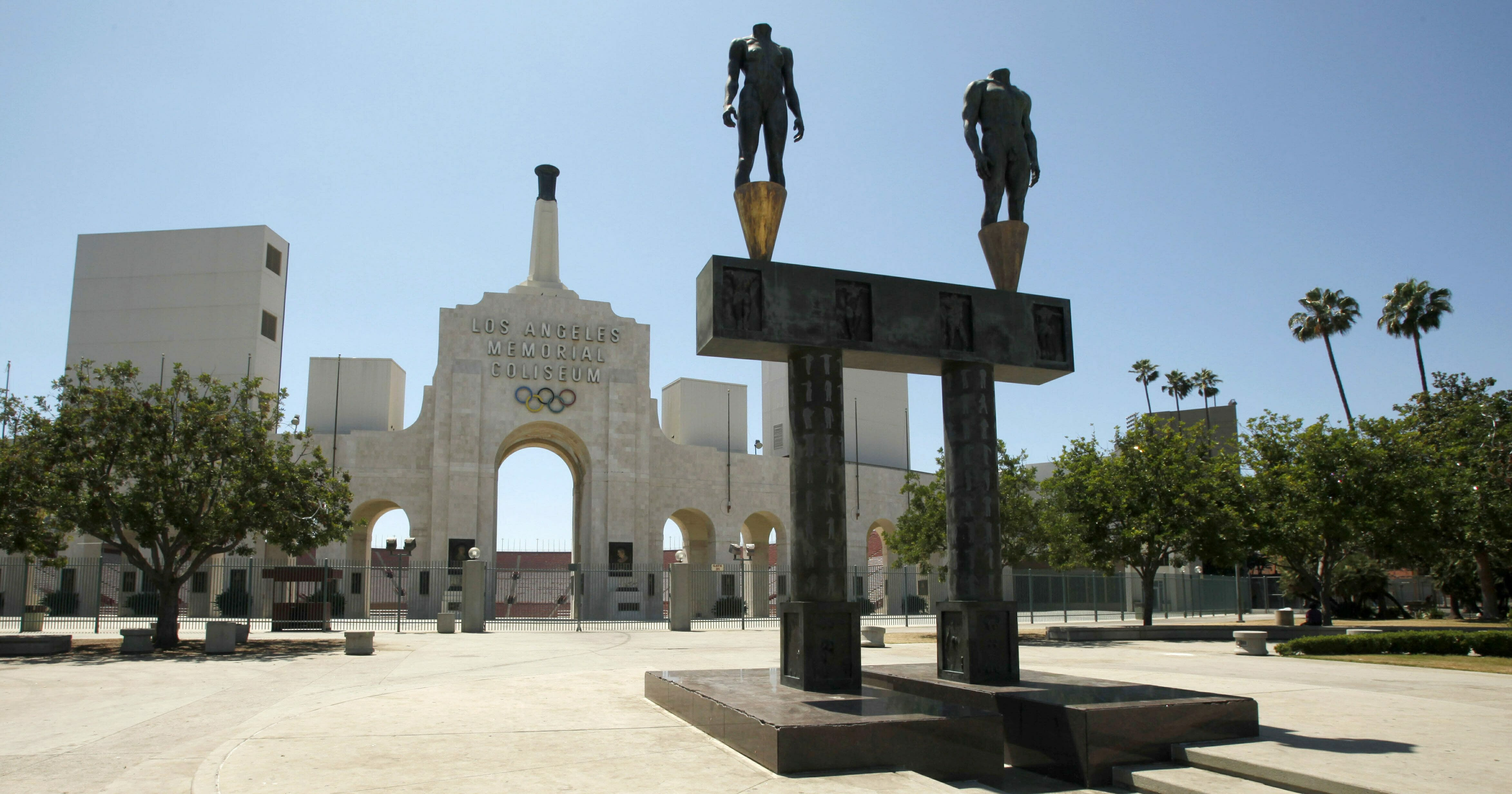 This July 1, 2009, file photo, shows the Los Angeles Memorial Coliseum with a pair of athlete statues installed for the 1984 Olympics, foreground, in Los Angeles.