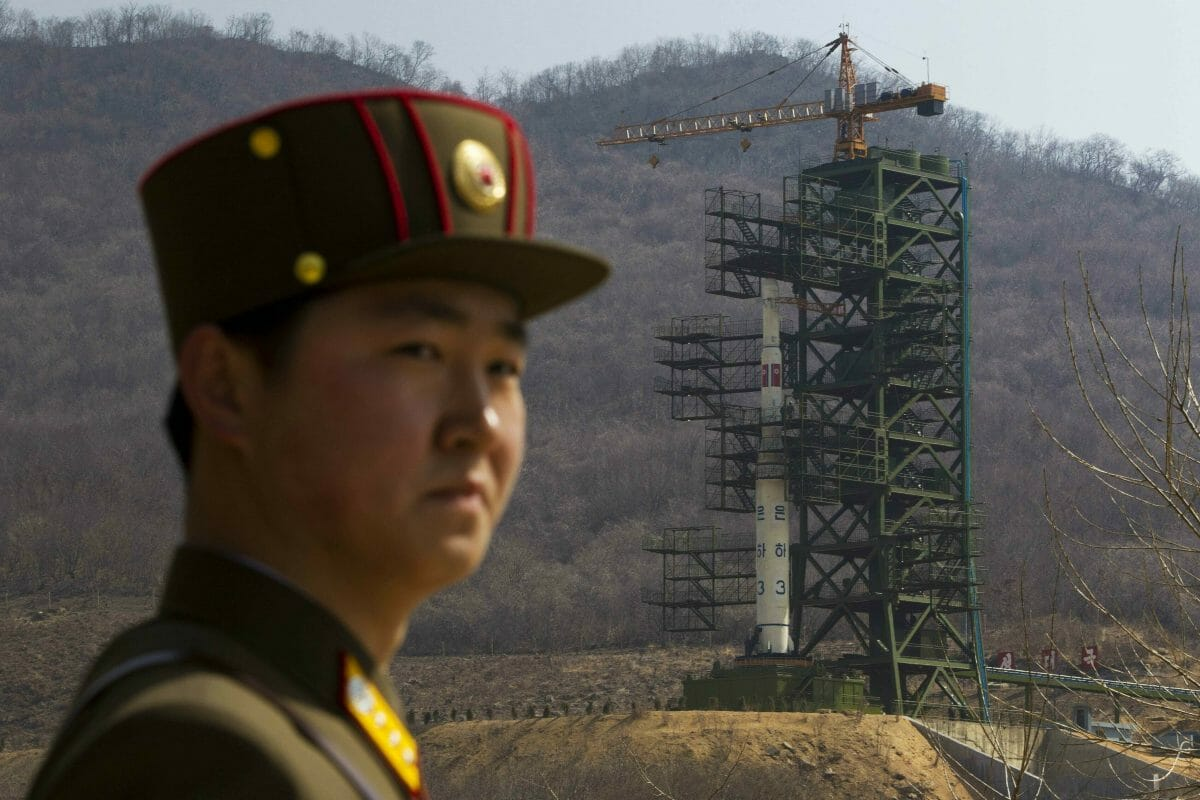 A soldier stands in front of the Unha-3 rocket at a launching site in Tongchang-ri, North Korea.