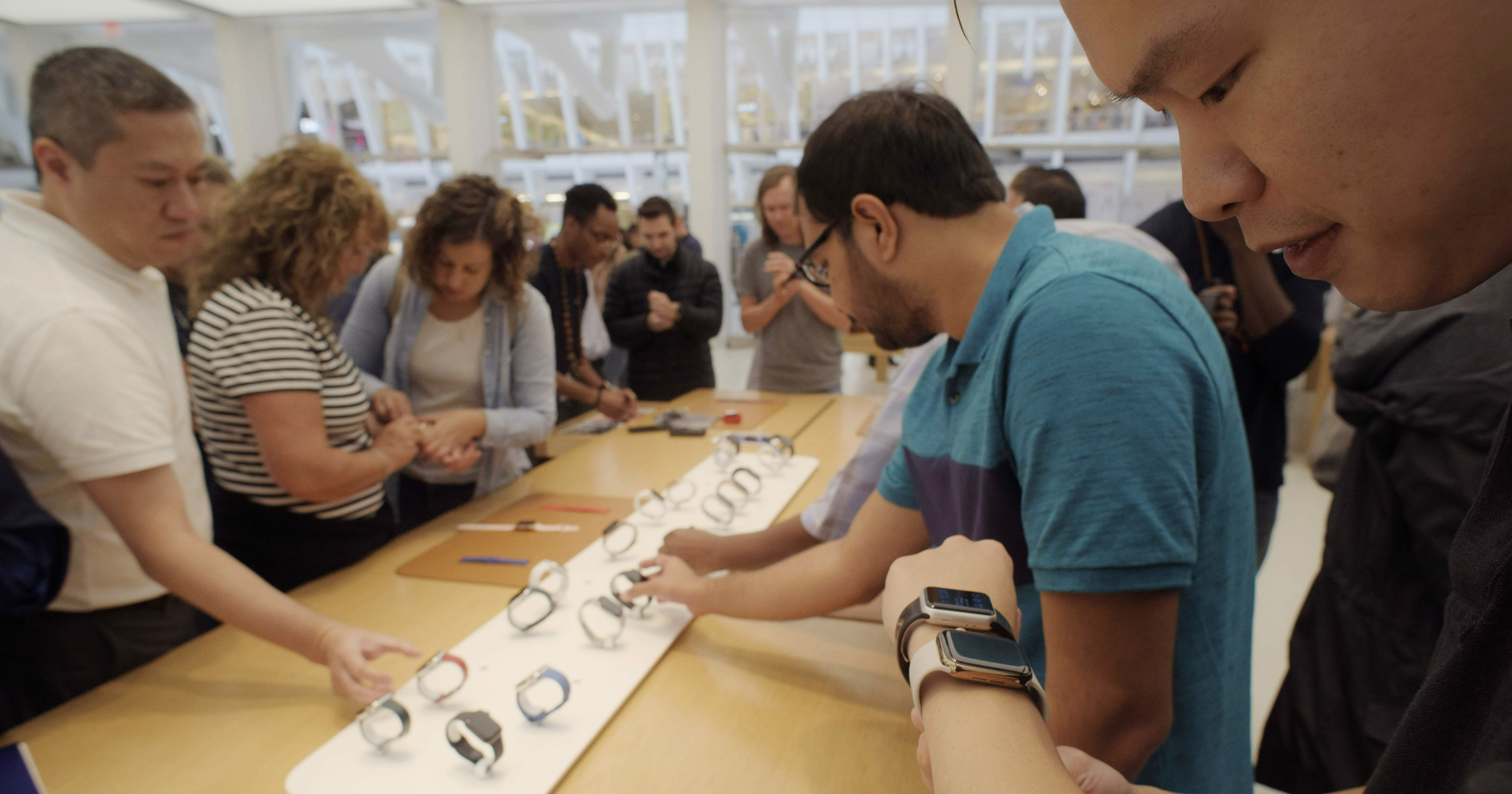 Customers look at Apple Watches at an Apple store in New York on Sept. 21, 2018.
