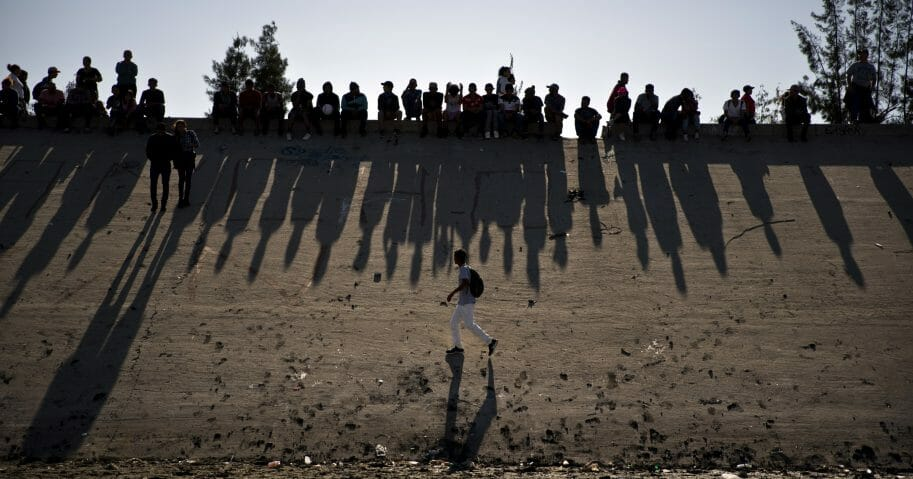 Migrants near the Chaparral border crossing watch clashes with U.S. border agents, seen from Tijuana, Mexico.