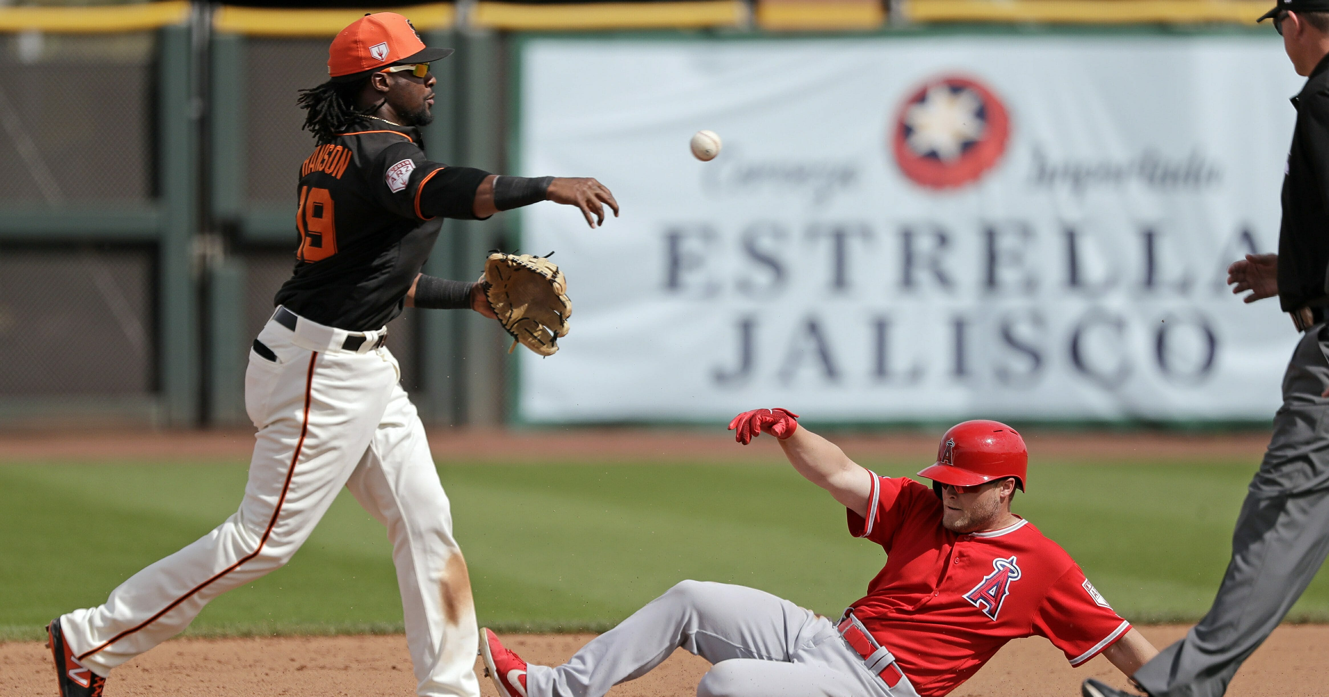 San Francisco Giants shortstop Alen Hanson, left, throws to first base after forcing out Los Angeles Angels' Brennon Lund at second base in the fifth inning of a spring training baseball game Friday, Mar. 15, 2019, in Phoenix.