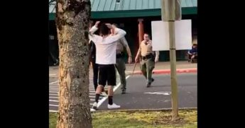 A Clark County, Washington, sheriff's deputy confronts an unruly crowd Friday at a middle school, where a disturbance turned into a near riot.