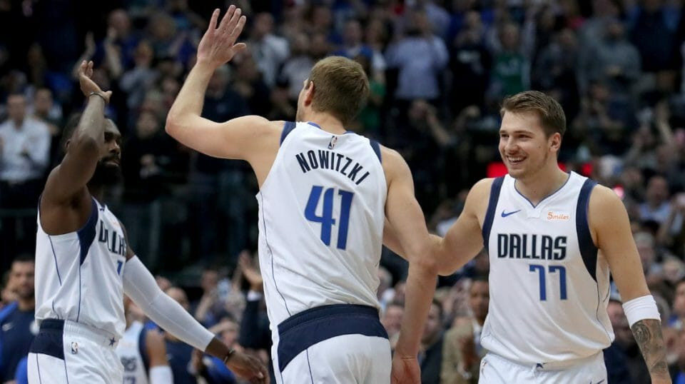 Dirk Nowitzki of the Dallas Mavericks celebrates with Tim Hardaway Jr. and Luka Doncic after scoring a basket against Kenrich Williams of the New Orleans Pelicans to become the sixth all-time leading scorer in the NBA at American Airlines Center on Mar. 18, 2019 in Dallas.
