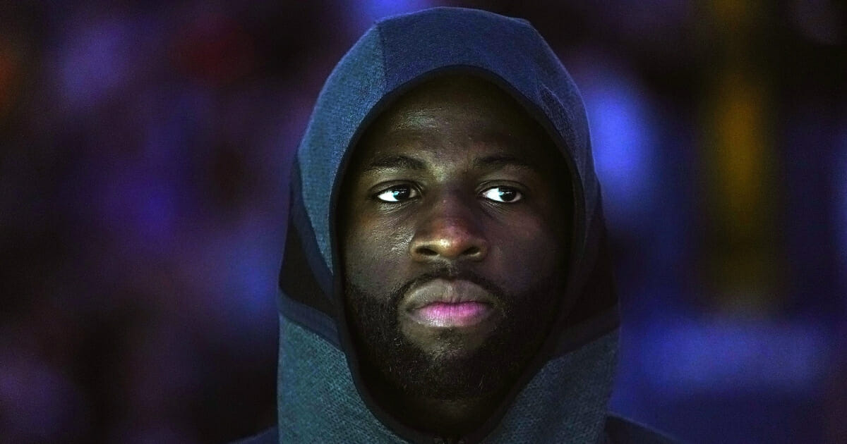 Draymond Green of the Golden State Warriors stands and looks on during the National Anthem prior to the start of an NBA basketball game against the San Antonio Spurs at ORACLE Arena on Feb. 6, 2019 in Oakland, California.