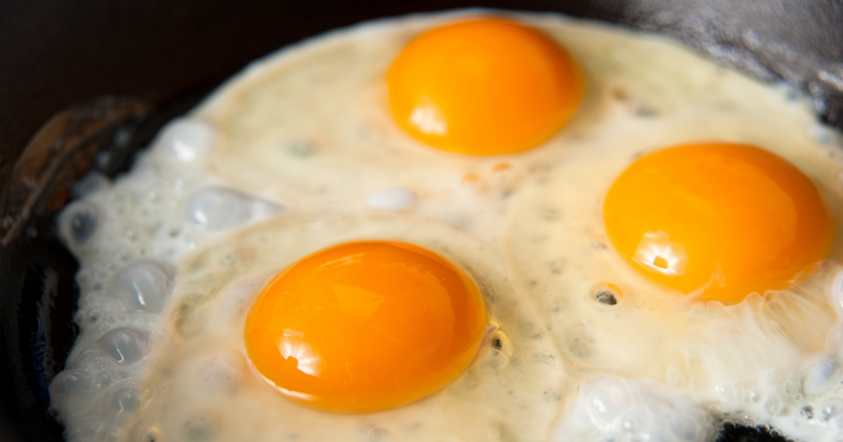 Three eggs being fried in a skillet.