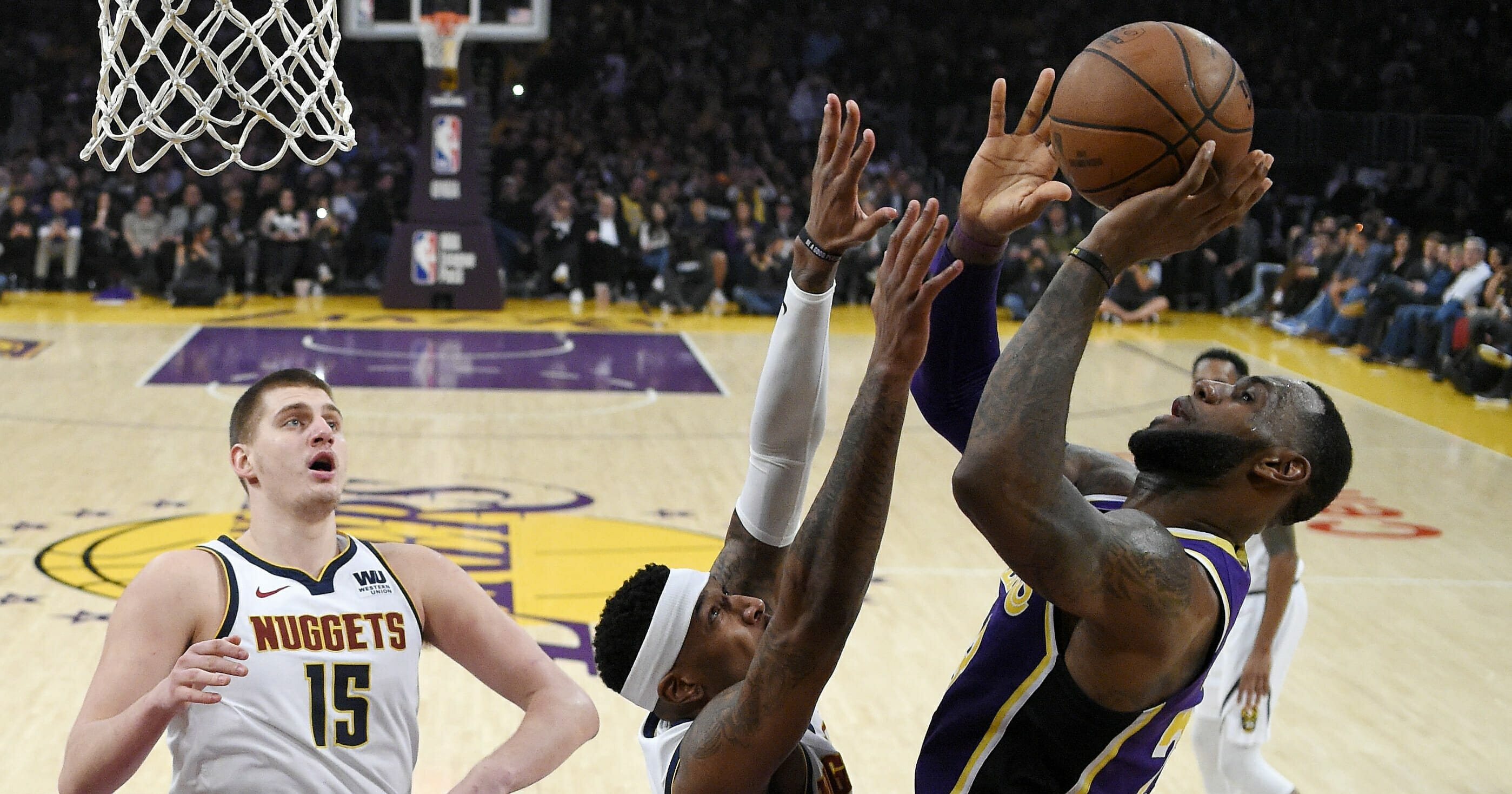 Los Angeles Lakers forward LeBron James shoots and scores against the Denver Nuggets on March 6, 2019 in Los Angeles