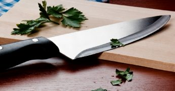A kitchen knife that has just cut parsley.