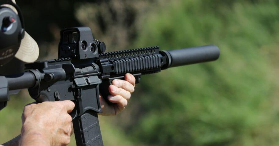 Man shooting gun with bump stock.