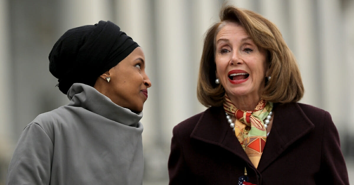 Rep. Ilhan Omar talks with Speaker of the House Nancy Pelosi during a rally with fellow Democrats before voting on H.R. 1.