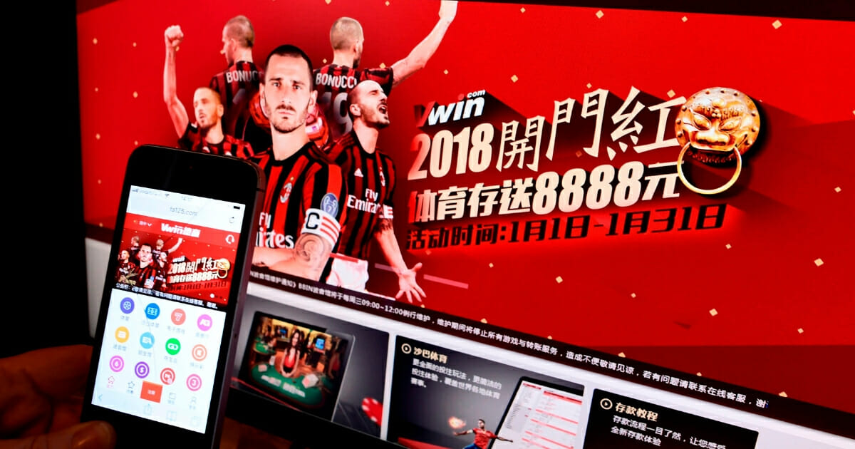 A picture taken on Jan. 8, 2018 in Milan shows the Asian online betting website Vwin on a smartphone and on a computer screen.