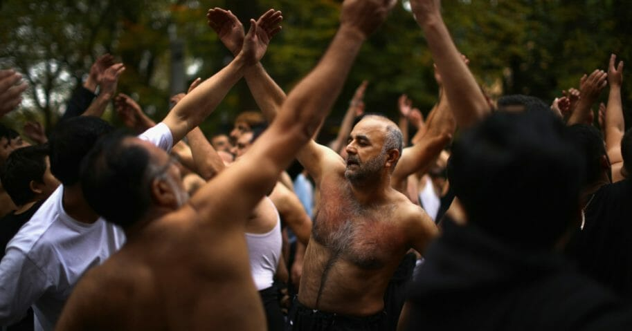 Shiite Muslim devotees beat their chests as they take part in a ritual self-flagellation.