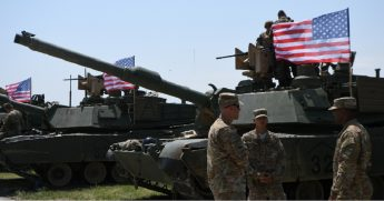 American soldiers stand near Abrams tanks bearing the U.S. flag before the opening ceremony of joint multinational military exercises outside Tbilisi, in the nation of Georgia in July 2017.