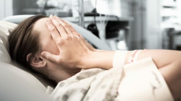 Young woman patient lying at hospital bed feeling sad and depressed worried.