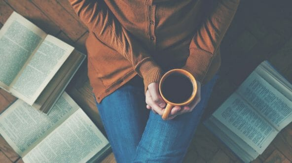 Girl having a break with a cup of fresh coffee surrounded by books.