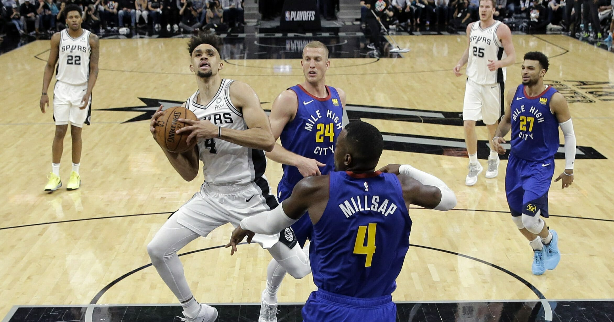 San Antonio Spurs guard Derrick White (4) drives to the basket against Denver Nuggets forward Paul Millsap (4) during Game 3 of their playoff series on April 18, 2019.