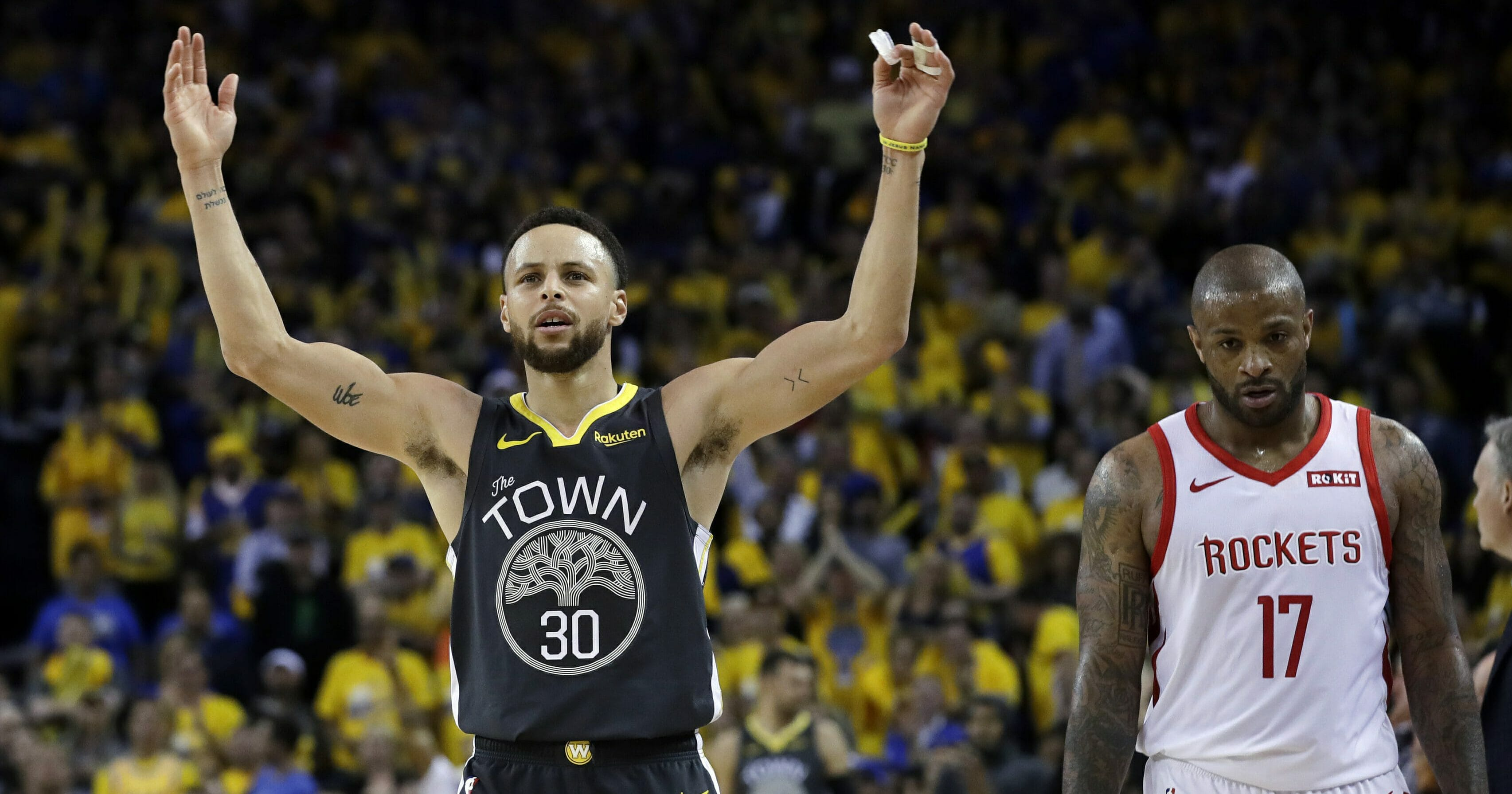 The Golden State Warriors' Stephen Curry, left, celebrates next to the Houston Rockets' P.J. Tucker.