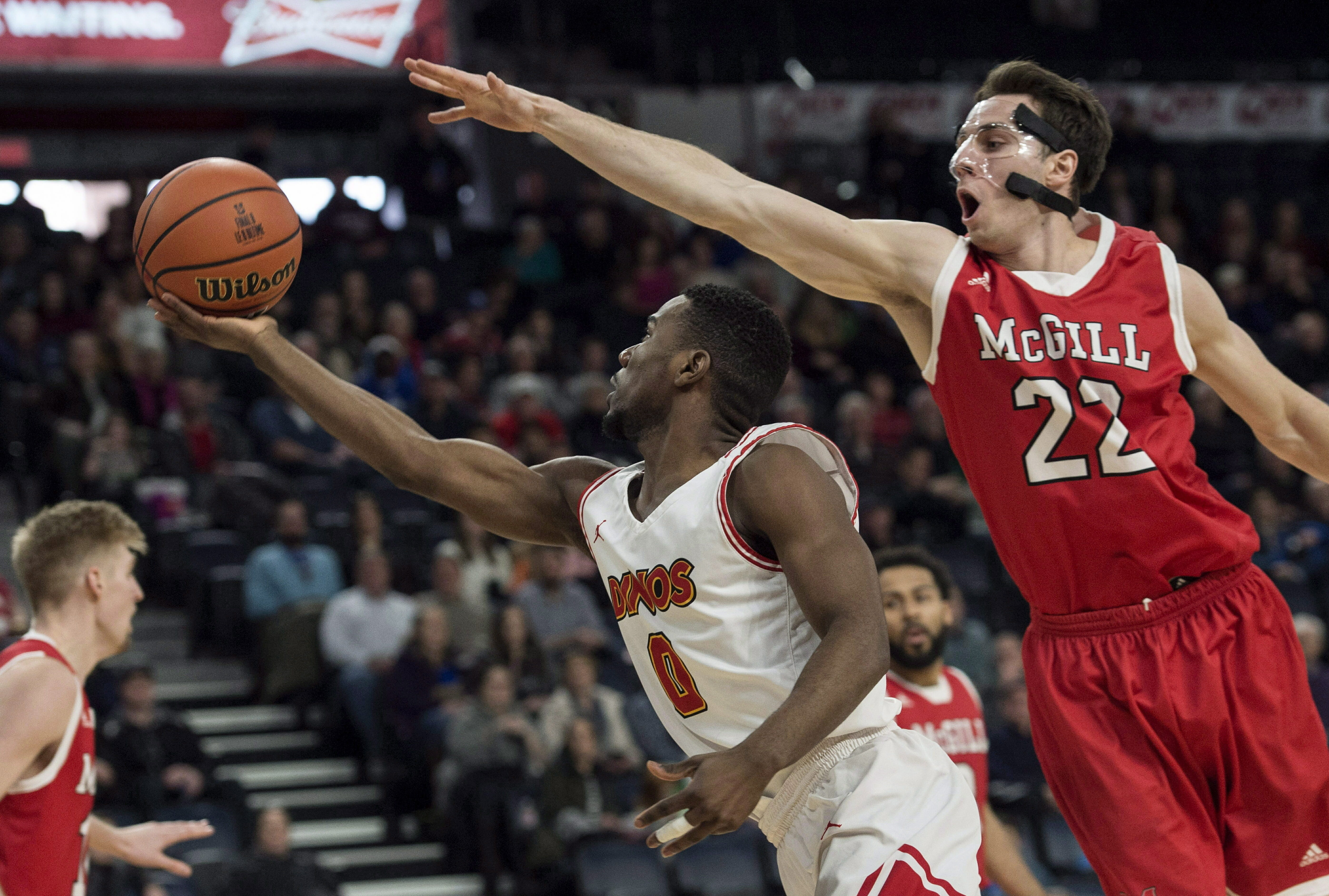 In this March 10, 2018 photo, Calgary's David Kapinga, left, shoots as McGill's Francois Bourque defends during the first half of in the semifinals of the men's basketball national championship in Halifax, Nova Scotia.