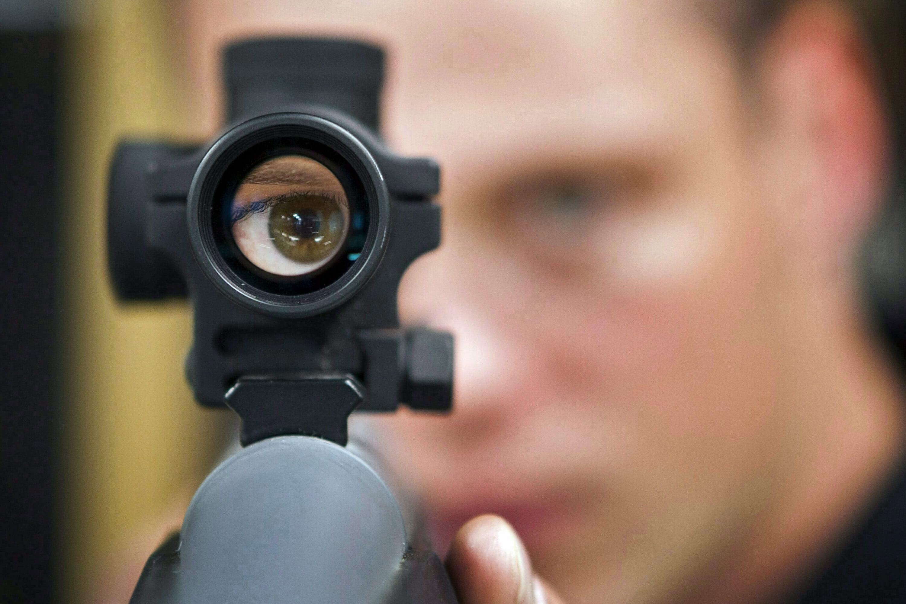 a man looks through the sights on a firearm