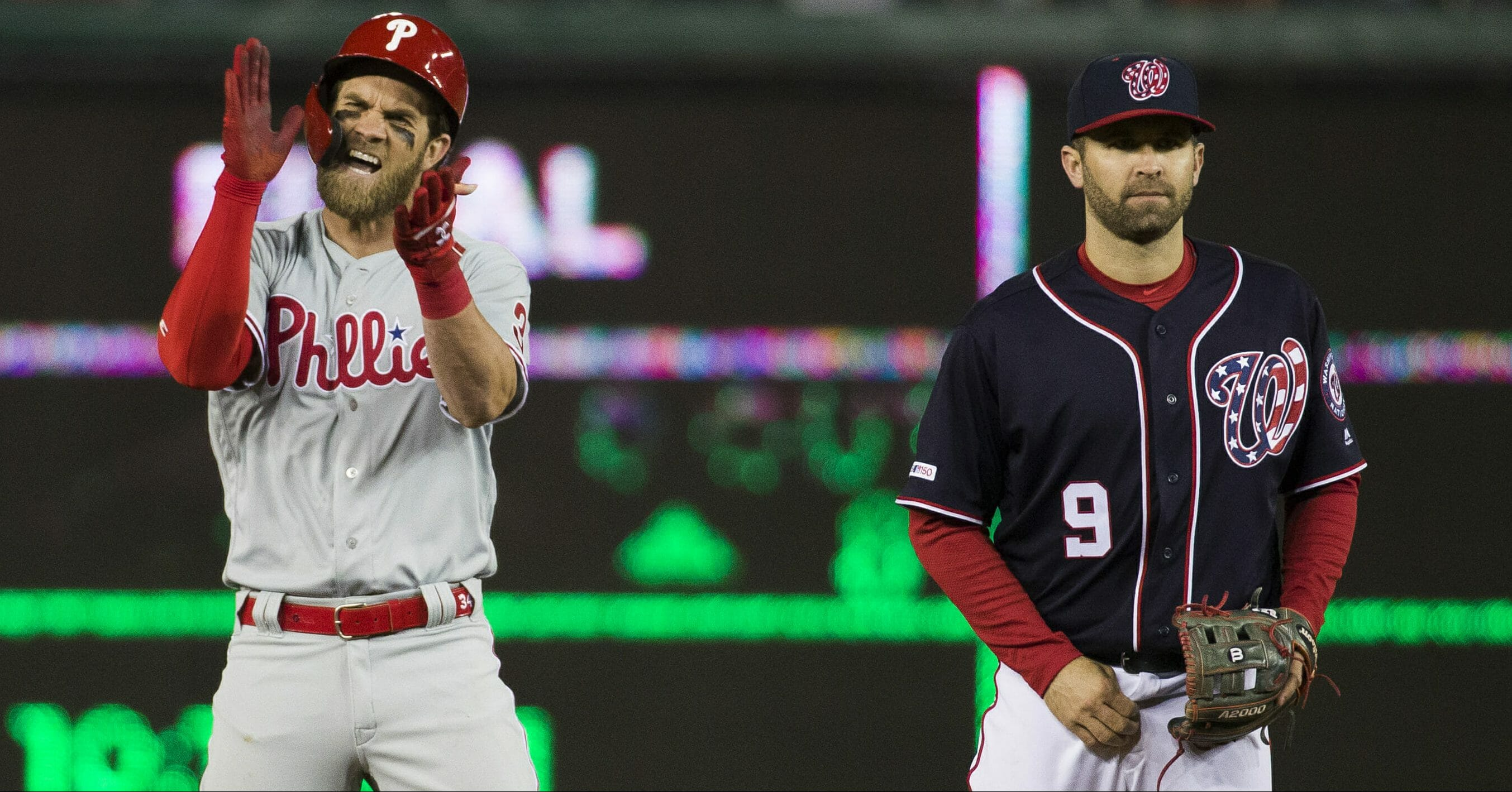 The Philadelphia Phillies' Bryce Harper, left, celebrates his RBI hit while on second base next to Washington Nationals second baseman Brian Dozier during the sixth inning April 2, 2019, at Nationals Park.