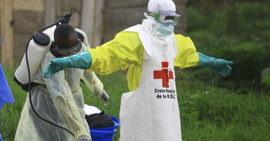 In this Sunday, Sept 9, 2018, file photo, a health worker sprays disinfectant on his colleague after working at an Ebola treatment center in Beni, eastern Congo.
