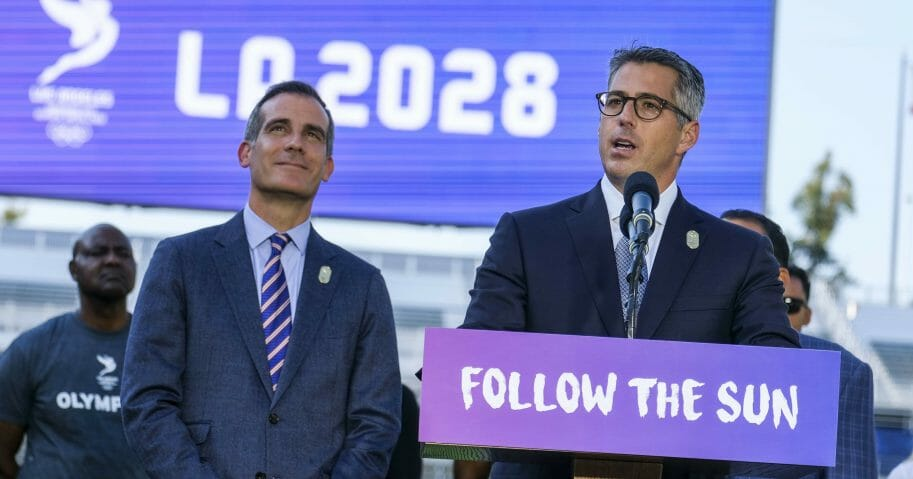 Los Angeles Mayor Eric Garcetti, left, listens as Los Angeles Olympic Committee leader Casey Wasserman speaks during a July 31, 2017, news conference to announce the city is hosting the 2028 Summer Games.