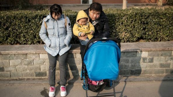 A couple and their child wait in the street of Beijing.