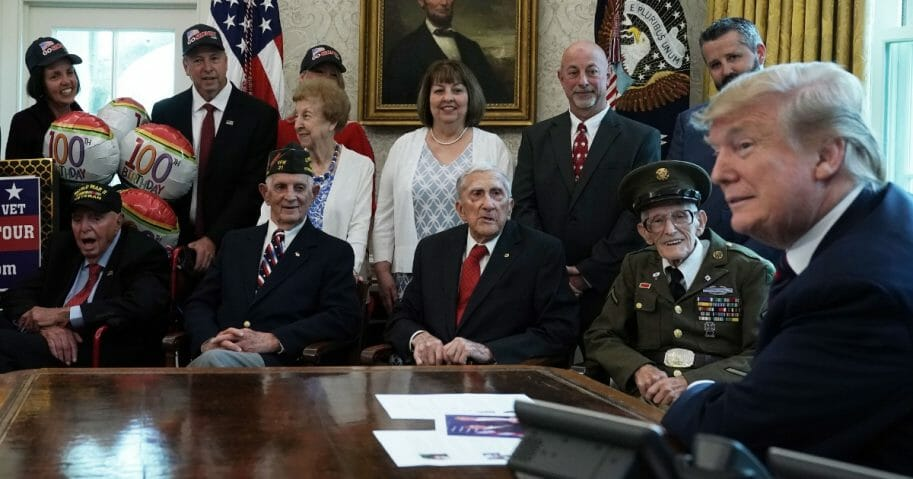 U.S. President Donald Trump meets with World War II veterans (L-R) Sidney Walton, Allen Jones, Paul Kriner and Floyd Wigfield in the Oval Office of the White House April 11, 2019, in Washington, D.C.