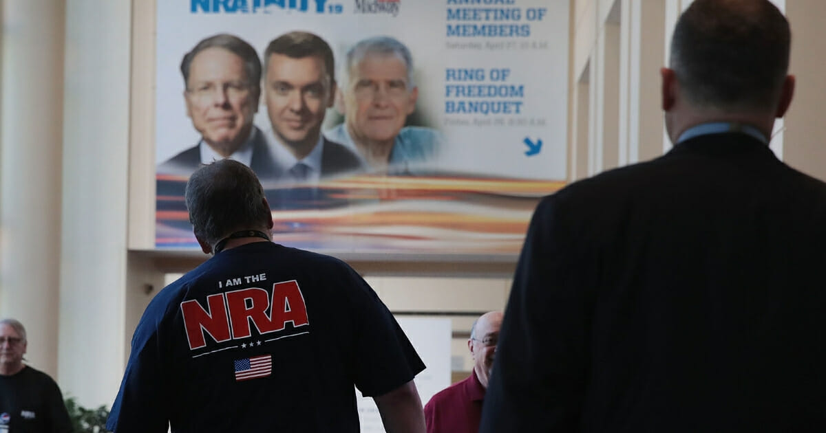Guests walk under a poster featuring Wayne LaPierre, Chris Cox and Oliver North at the 148th NRA Annual Meetings & Exhibits on April 27, 2019, in Indianapolis.
