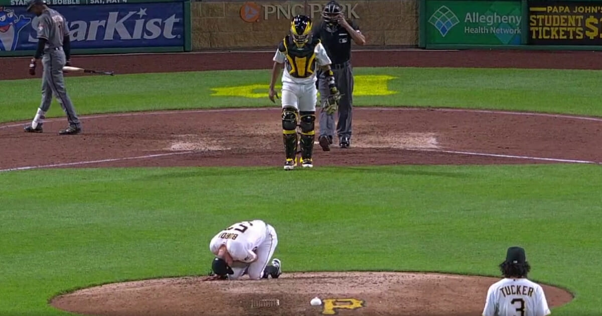 Nick Burdi of the Pittsburgh Pirates fell to the mound in pain after injuring his pitching arm in a 12-4 loss to the Arizona Diamondbacks.