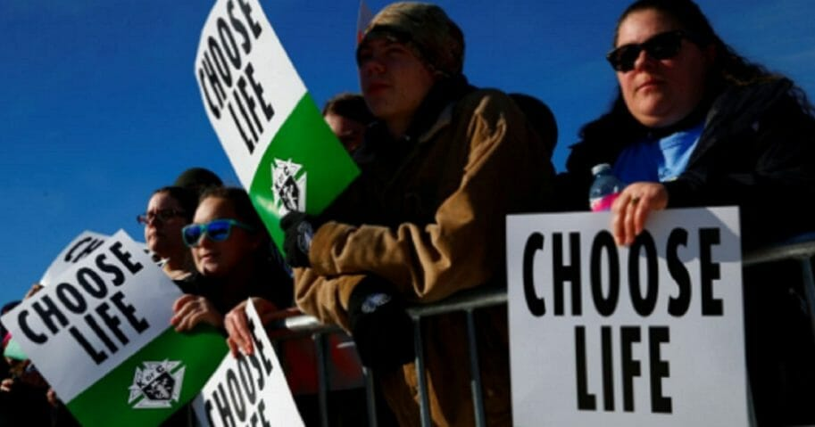 "Pro-life demonstrators carry signs that say ""Choose Life."""