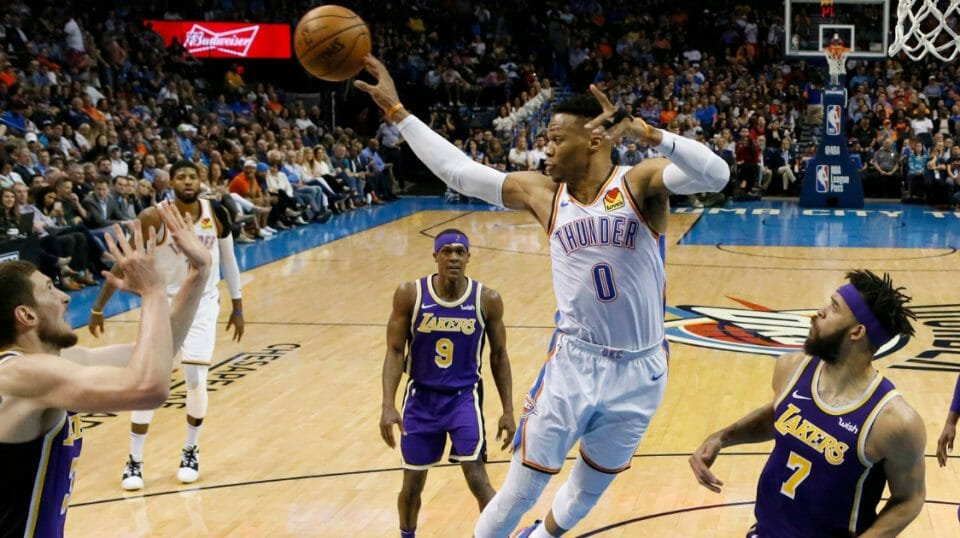 Oklahoma City Thunder guard Russell Westbrook passes to a teammate between Los Angeles Lakers forward Mike Muscala, left, guard Rajon Rondo and center JaVale McGee on April 2, 2019, in Oklahoma City.