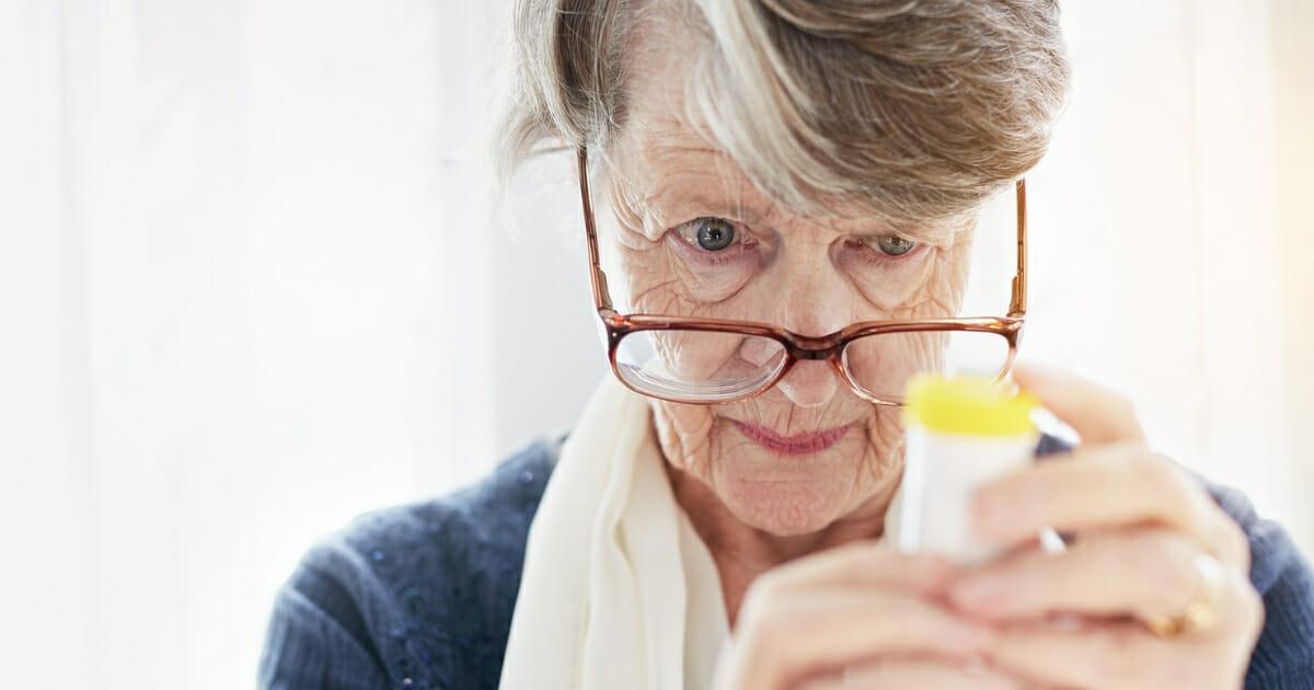 A woman holds a pill bottle.