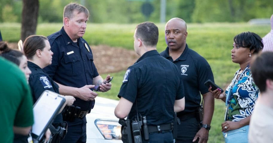 Police officers consult after a shooting Tuesday on the campus of the University of North Carolina at Charlotte.