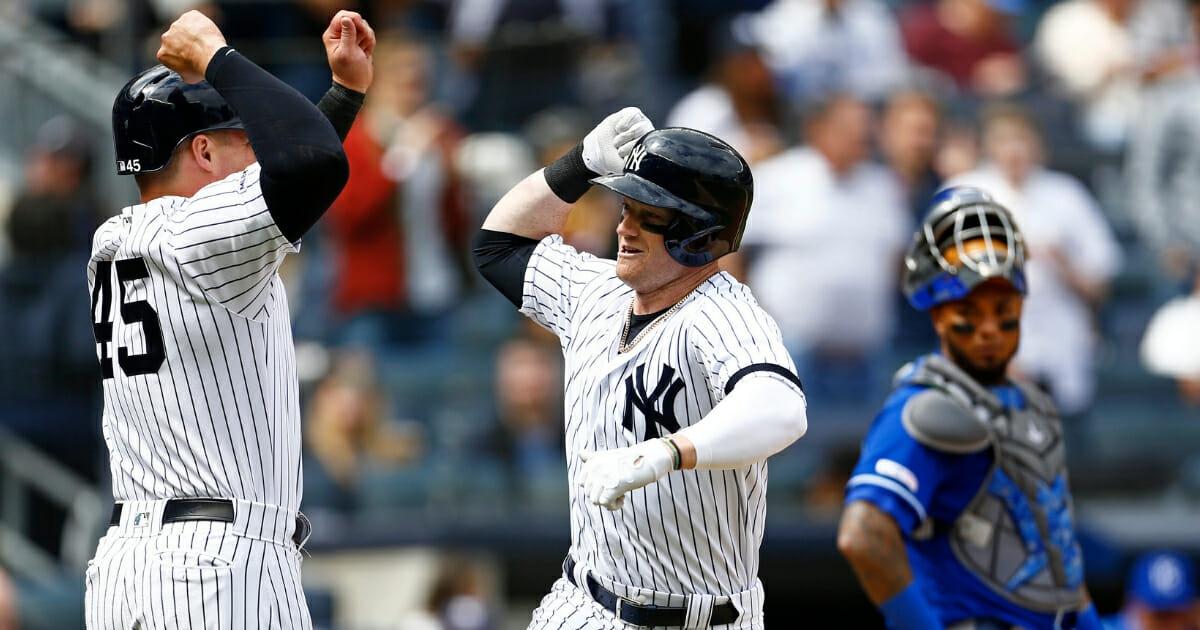 The New York Yankees' Clint Frazier, center, celebrates his three-run home run with Luke Voit in front of Kansas City Royals catcher Martin Maldonado on April 21, 2019.