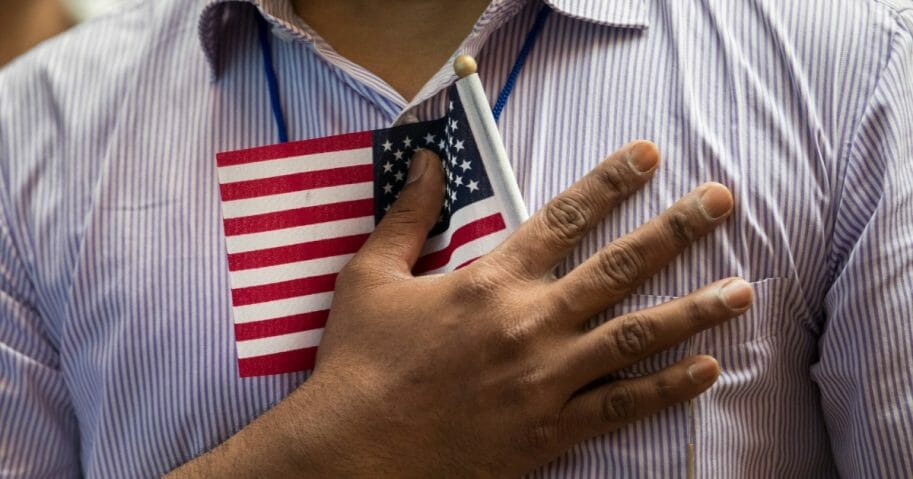 Man holding small American flag on his chest.