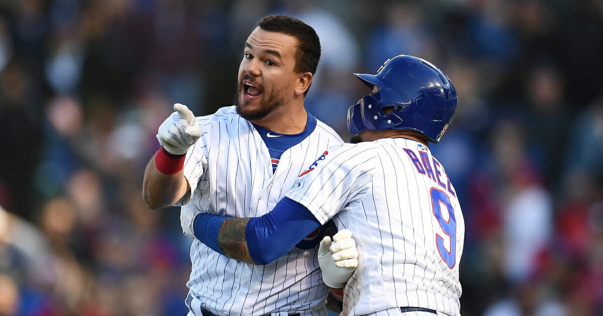 Kyle Schwarber of the Chicago Cubs is restrained by Javier Baez after being called out by the third base umpire during the ninth inning of a game against the Los Angeles Angels at Wrigley Field on April 13, 2019 in Chicago.