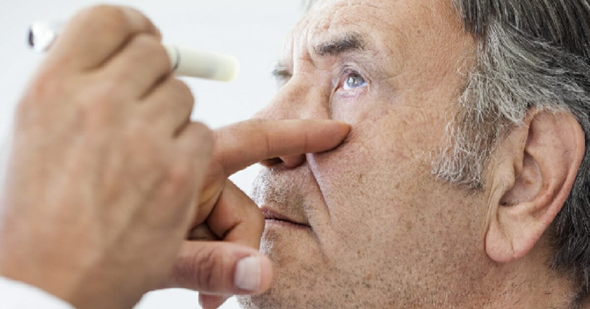 An opthallmologist examines a patient.