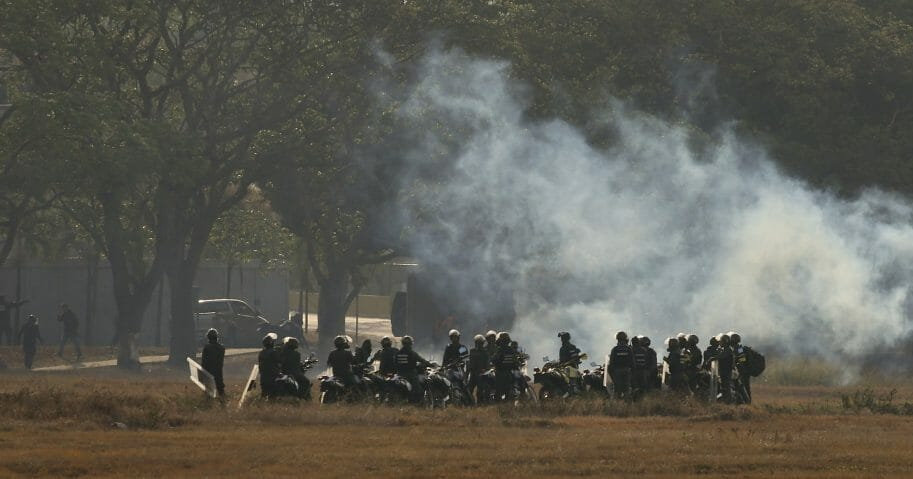 Troops loyal to Venezuelan President Nicolas Maduro stand amid tear gas they fired from inside La Carlota airbase.