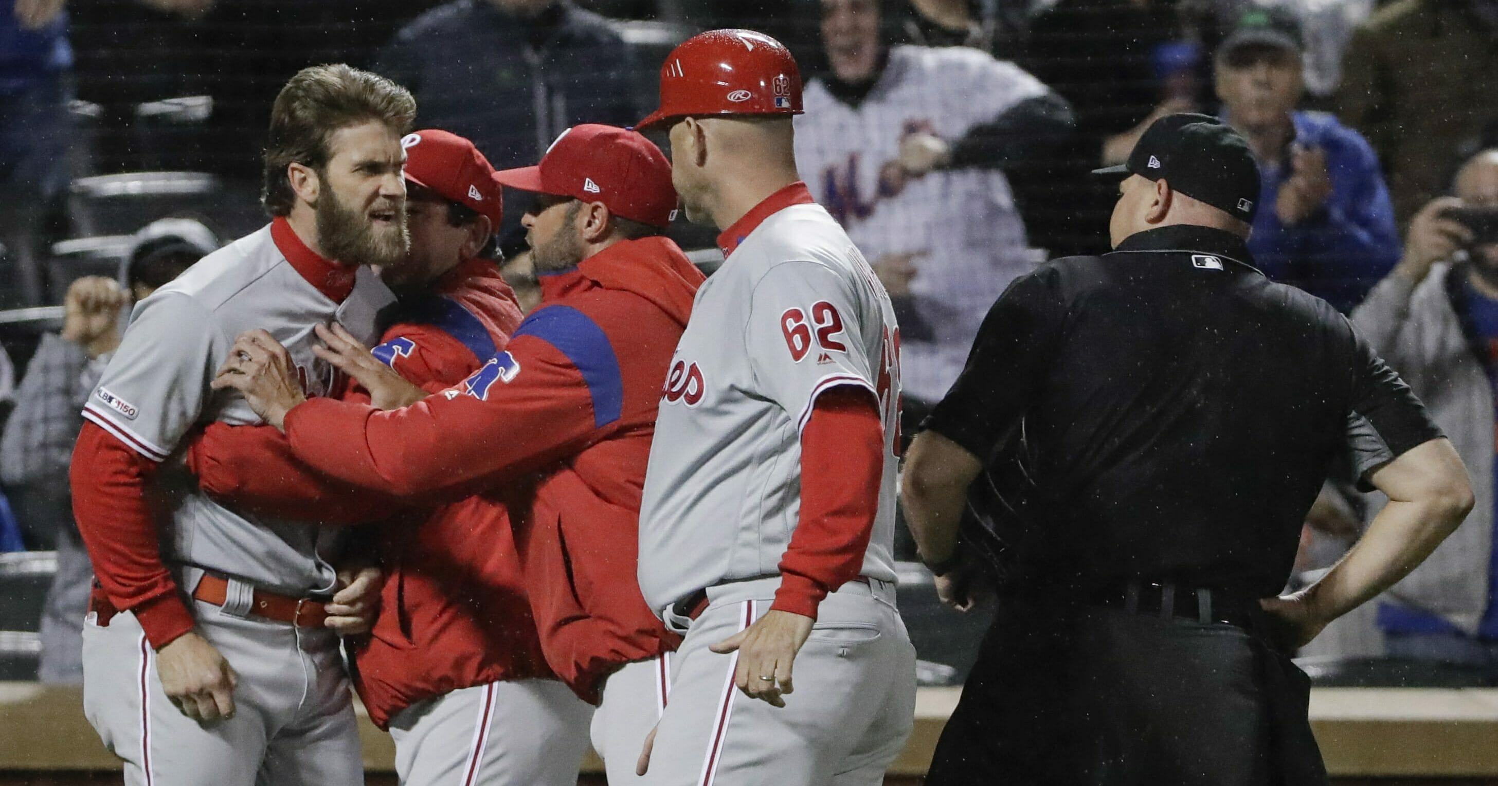 Philadelphia Phillies' Bryce Harper, left, is restrained while arguing with umpire Mark Carlson, right, during the fourth inning of a baseball game against the New York Mets, Monday, April 22, 2019, in New York.