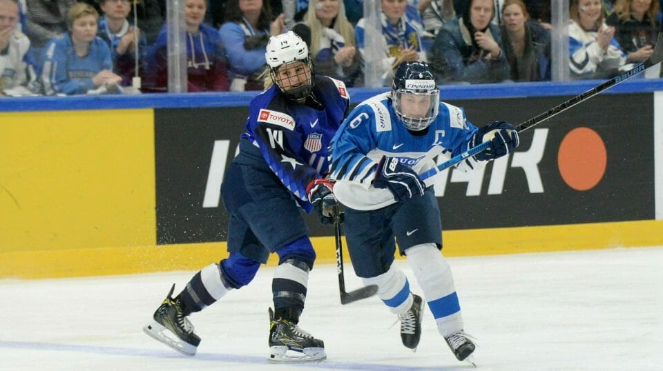 Brianna Decker, left, of the United States and Jenni Hiirikoski of Finland vie for the puck during the IIHF Women's Ice Hockey World Championships final match between the United States and Finland in Espoo, Finland, Sunday, April 14, 2019.