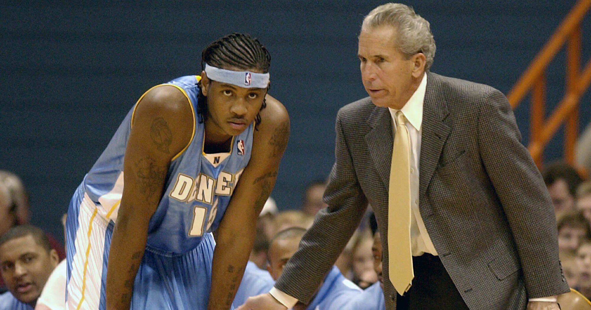 In this Sunday, Oct. 19, 2003, file photo, Denver Nuggets' Carmelo Anthony, left, receives instructions from assistant coach John MacLeod in the second period of a preseason game against the Detroit Pistons in Syracuse, N.Y.