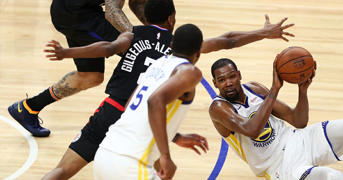 Kevin Durant of the Golden State Warriors looks for a pass against Shai Gilgeous-Alexander of the Los Angeles Clippers during the third quarter at Staples Center on April 18, 2019 in Los Angeles.