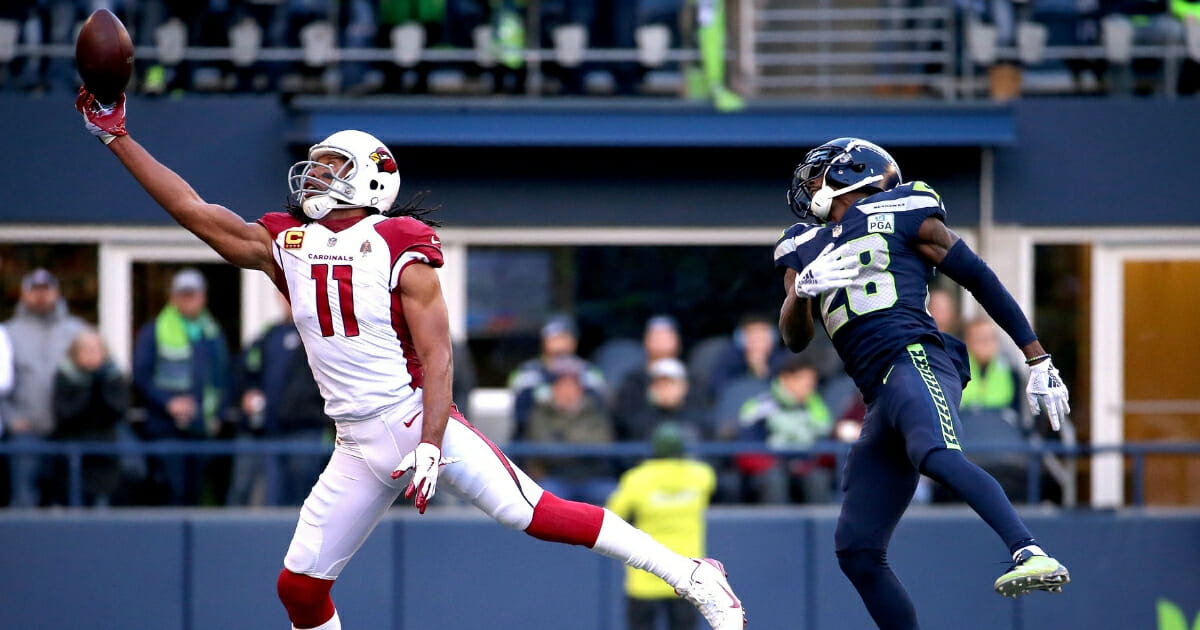 Larry Fitzgerald of the Arizona Cardinals reaches for a pass against Justin Coleman of the Seattle Seahawks in the second quarter during their game at CenturyLink Field on Dec. 30, 2018 in Seattle.