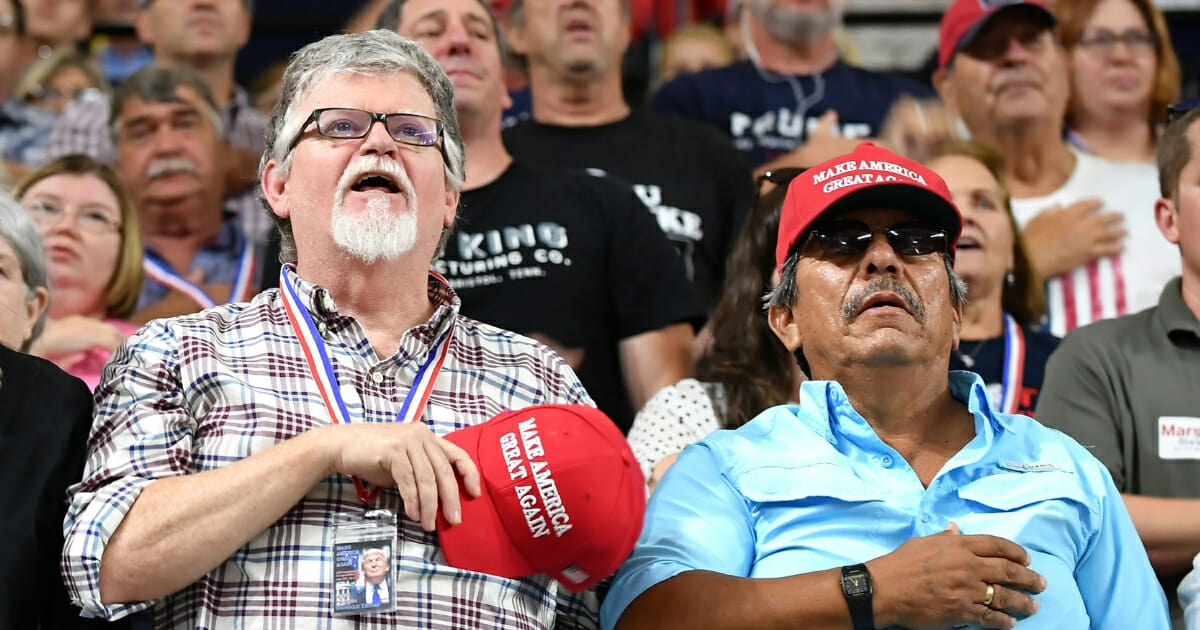 Supporters recite the Pledge of Allegiance prior to President Donald Trump speaking at a rally.