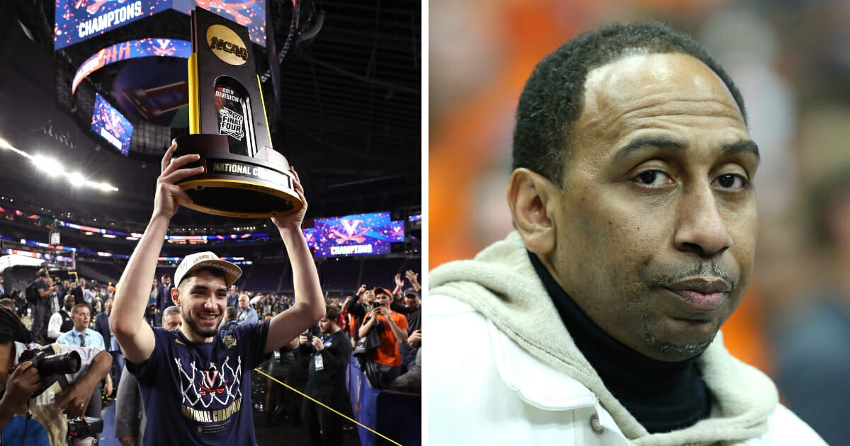 Ty Jerome, left, of the Virginia Cavaliers celebrates with the trophy after winning 2019 NCAA men's Final Four National Championship. ESPN host Stephen A. Smith, right, looks on prior to the game between the Duke Blue Devils and the Syracuse Orange.